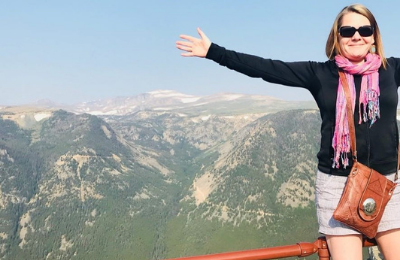Deborah Nicholson standing with her arms out in front of a mountain range on a holiday